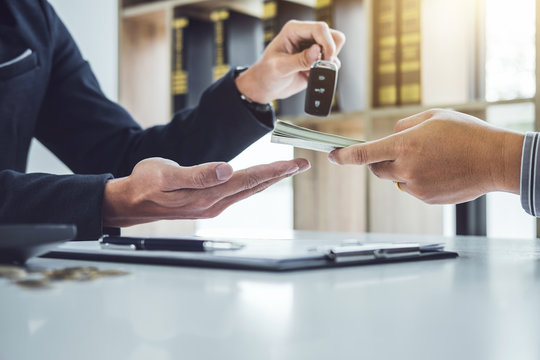 Salesman send key to customer after good deal agreement and receive money, successful car loan contract buying or selling new vehicle