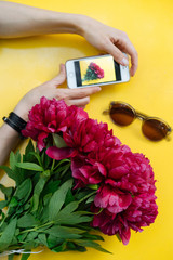 Hands holding smartphone with bouquet photo