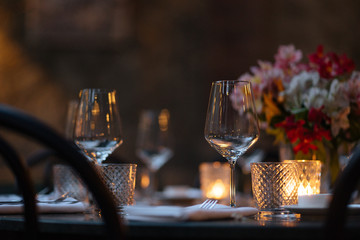 Close up of wine glasses placed on table with candle and bouquet