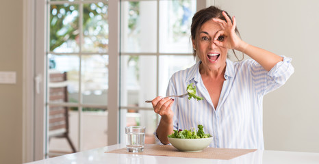 Middle aged woman eating fresh salad in a bowl at home with happy face smiling doing ok sign with hand on eye looking through fingers