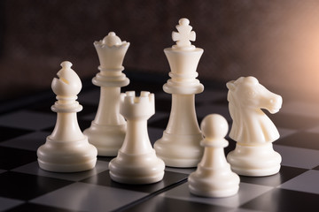 the abstract image of the Staunton chess set such as king, bishop, queen, knight, rook, pawn placed on chess board. the concept of strategy, victory, business, games, intelligence.