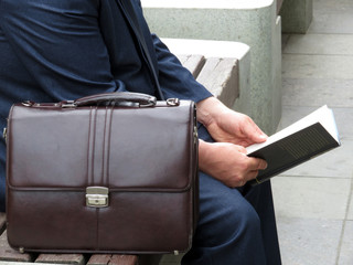A man in a business suit with a leather briefcase on a bench reading a paper book. Concept for  businessman or official, skills development, advanced training, self-education
