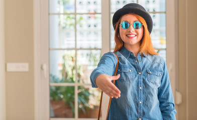 Stylish redhead woman wearing bowler hat and sunglasses smiling friendly offering handshake as greeting and welcoming. Successful business.