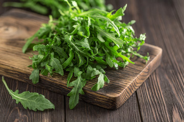Spoed Fotobehang Kruiderij Fresh green arugula in bowl on table. Arugula rucola for salad. Close up of fresh green healthy food. Diet concept.