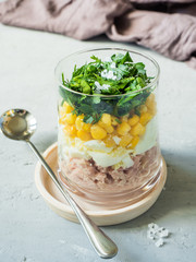 Fresh tuna salad with egg corn greens in a glass Cup on a concrete table. copy space