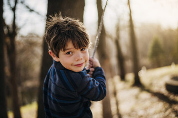 Portrait of boy playing on rope swing
