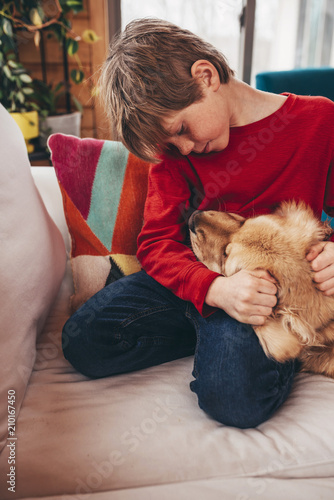 Boy Sitting On Couch Hugging His Golden Retriever Dog Stock Photo