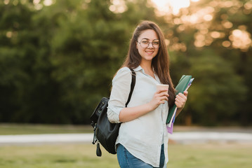 A young girl student in round glasses prepares for the entrance exams to the university. Listens to an online lecture and drinks coffee in the backyard of the university building Wall mural