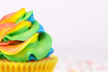 Cupcake with rainbow colorful cream in yellow cup on white wooden table decorated with colorful sprinkles. Close up.
