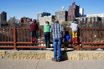 Father standing on Stone Arch bridge looking at cityscape with his four children, Minneapolis, Minnesota, America, USA