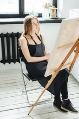young woman in black clothes and an apron sits in a bright room and paints pictures, brushing oil paints on canvas with malbert