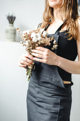 woman artist in dark clothes holding a bouquet plant cotton