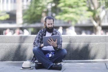 Man sitting on his skateboard using a digital tablet