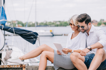 smiling young couple in sunglasses sitting and using digital tablet near yacht Fototapete