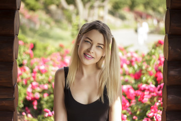 Art portrait of a beautiful woman with a charming smile on the background of roses