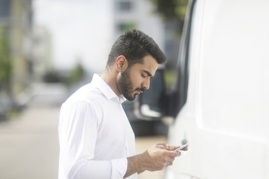 Man standing in the street checking his mobile phone