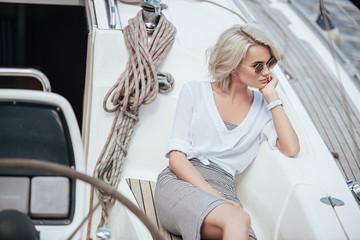 high angle view of pensive blonde girl in sunglasses sitting on yacht and looking away