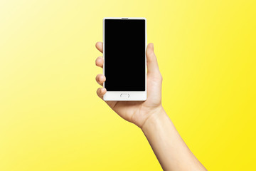 Mockup of female hand holding frameless cell phone with black screen isolated at yellow background.