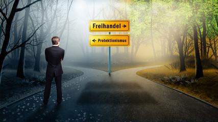 Geschäftsmann steht an Straßenkreuzung von Freihandel und Protektionismus