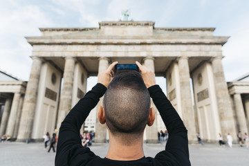 young man taking a picture of the Brandenburg Gate