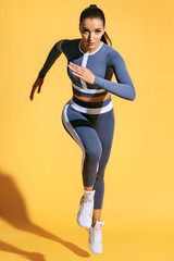 Beautiful woman runner in silhouette on yellow background. Photo of sporty woman in fashionable sportswear. Dynamic movement. Strength and motivation. Full length