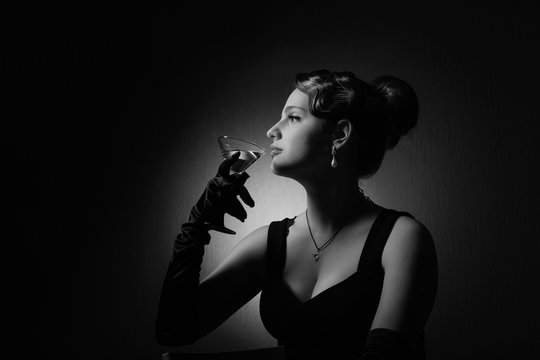 Dramatic portrait of a beautiful woman with glass of martini .
