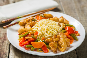 Deep-fried squid with vegetables in garlic sauce with noodles. Concept of Chinese cuisine.