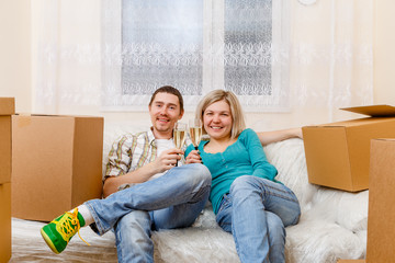 Photo of man and woman with wine glasses with wine sitting on sofa among cardboard boxes