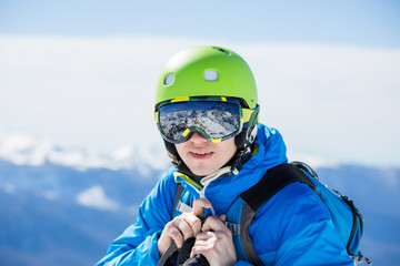 Photo of man in helmet and glasses with reflection of mountains on winter day