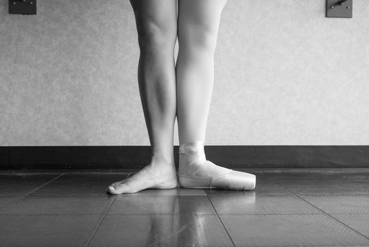 Black and white version of a ballet dancer in first position with one foot in a pointe shoe, and one bare leg