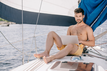 handsome shirtless man in swim trunks using laptop on yacht