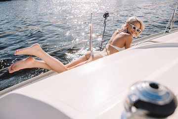 beautiful young woman in bikini relaxing and having sunbath on yacht