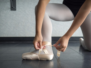 Recreational young female ballet dancer ballerina, in the studio putting on her pointe shoes, tying up her ribbons