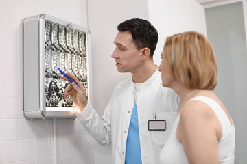 Orthopedist and patient looking at MRI scan in hospital