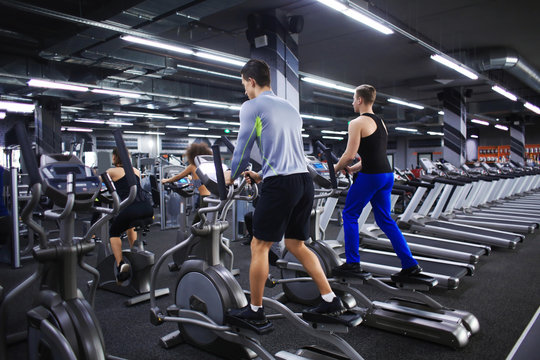 People exercising on training machines in gym