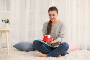 Beautiful young woman with gift box at home