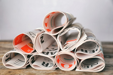 Rolled newspapers on wooden table