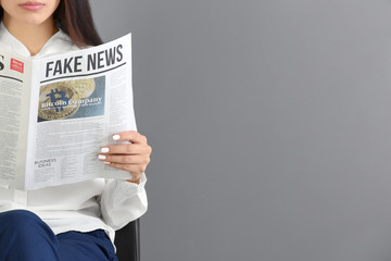 Young woman reading newspaper against grey background