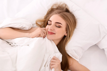 Young woman in bed at home