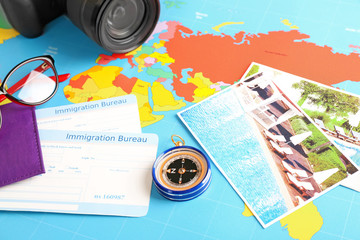 Composition with compass and immigration bureau cards on world map. Travel planning concept