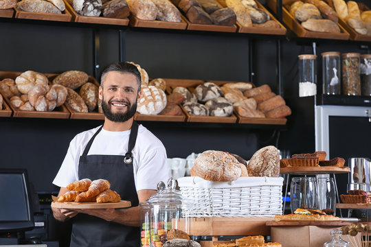 Male baker holding wooden board with delicious croissants in shop