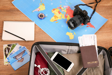 Composition with packed suitcase, map and camera on wooden background. Travel concept