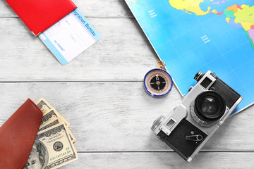 Composition with map, camera,money and passport on wooden background. Travel concept