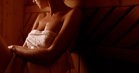 girl in a spa treatment in a traditional sauna with a brush for skin and a washcloth. relaxes wrapped in a white towel