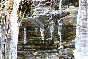 The thawing icicles with the falling water drop in the mountains