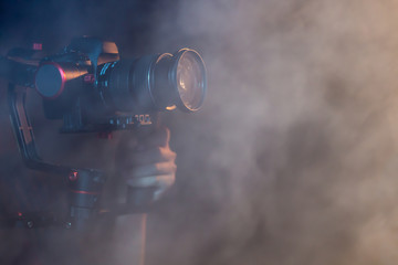 object for smooth video production to make movie . camera stability automatic system , electric machine . professional film maker with gimbal . closeup abstract smoke scene background .