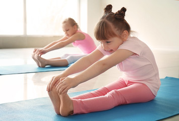 Little children practicing yoga indoors Wall mural