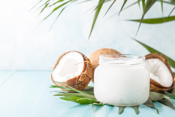 Coconut oil and coconuts on a bright pastel background.