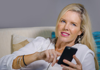 beautiful happy blond woman early 40s relaxed at home living room using internet social media on mobile phone smiling lying comfortable on sofa couch
