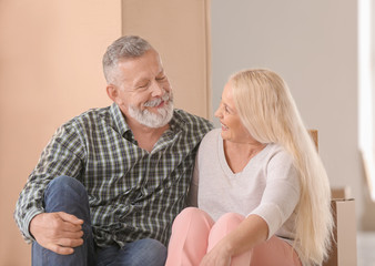Mature couple with belongings indoors. Moving into new house